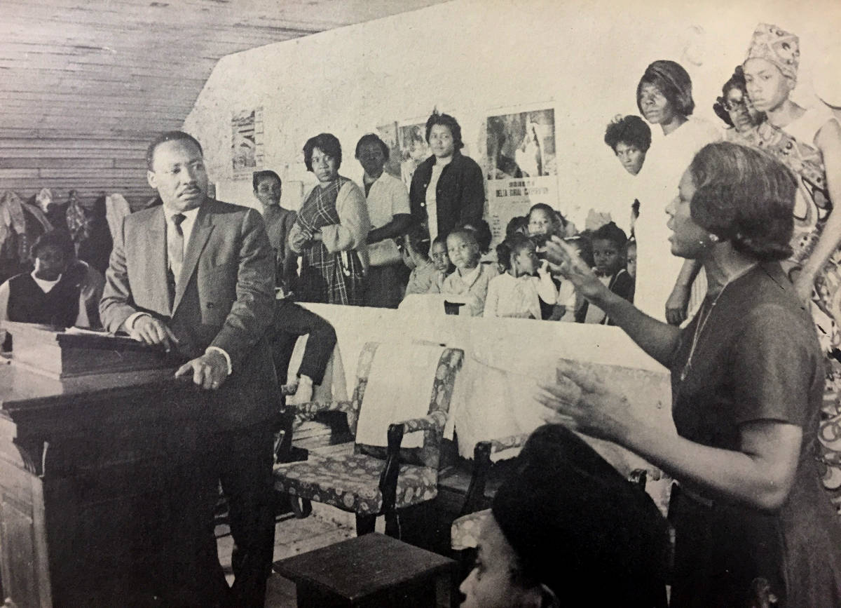 Rev. Dr. King listens as a woman speaks in a crowded classroom.